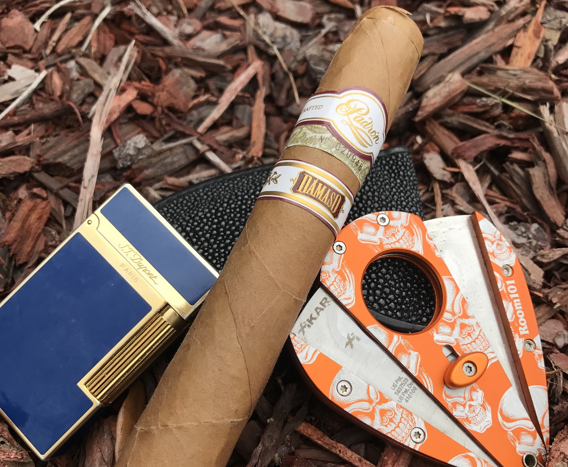 A Padron Cigar with a cigar cutter and lighter on wood chippings