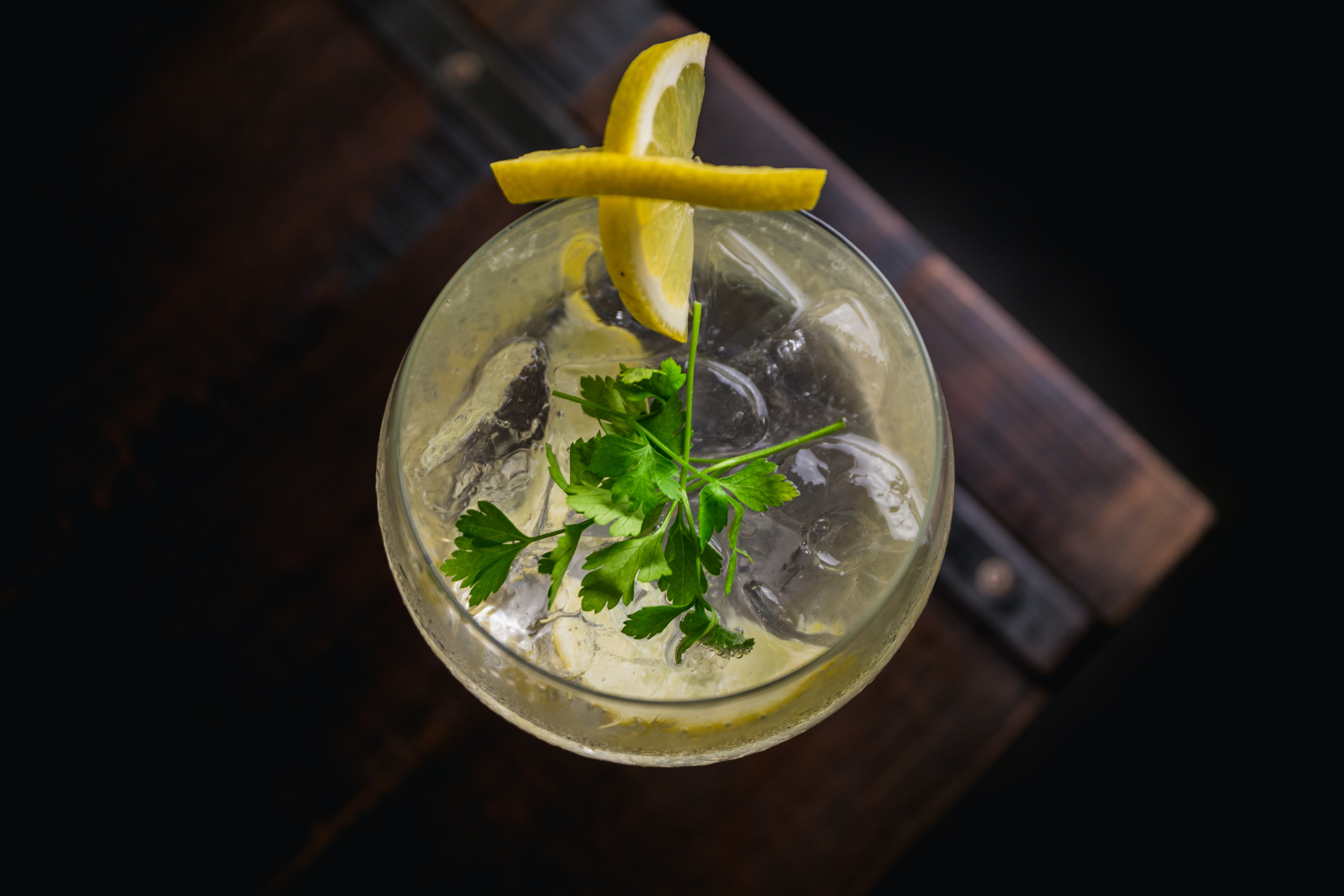 A glass of gin garnished with lemon and coriander