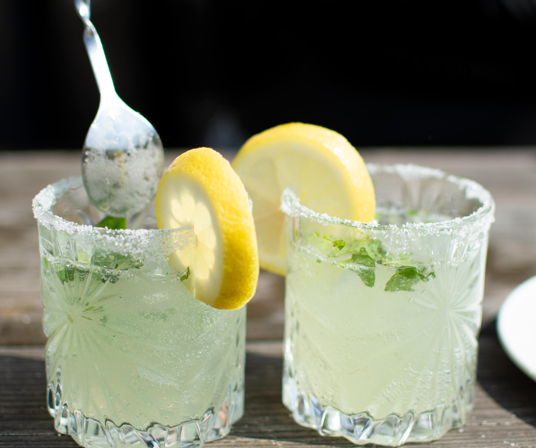 two glasses of bitter lemon garnished with lemon