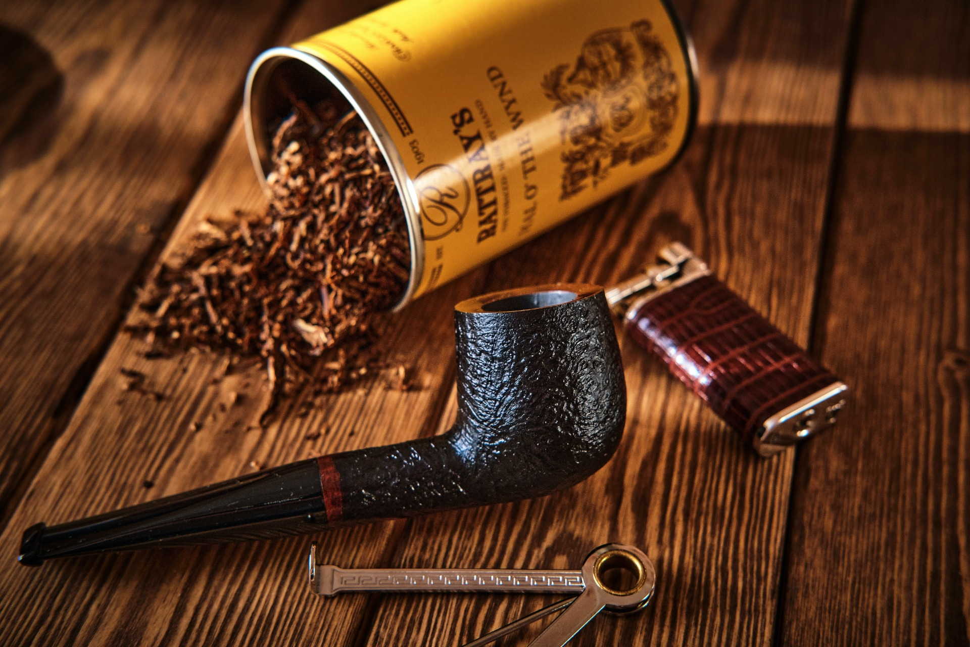 A pipe, a lighter and a spilt tin of tobacco