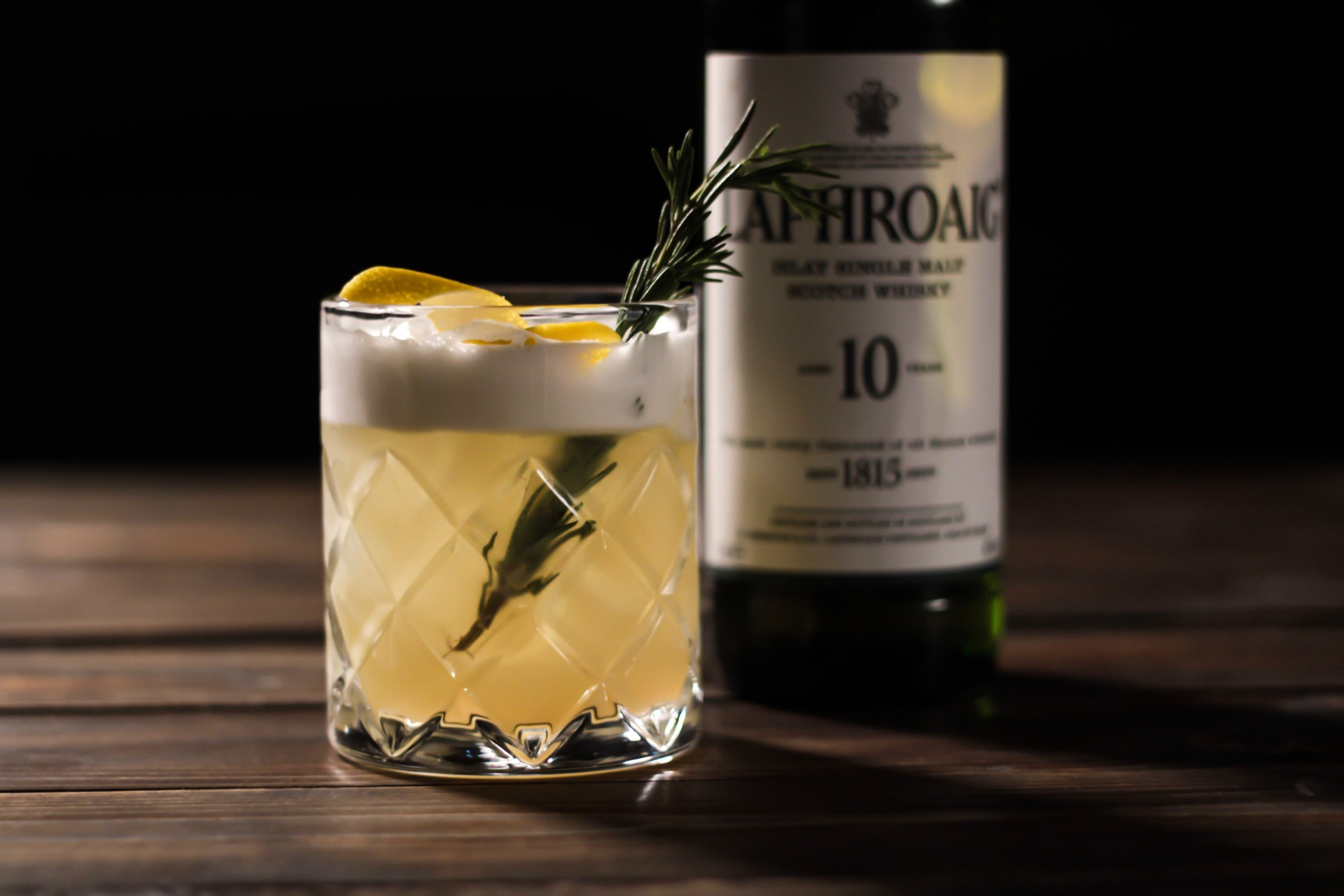 A cocktail of Laphroaig with a bottle in the background