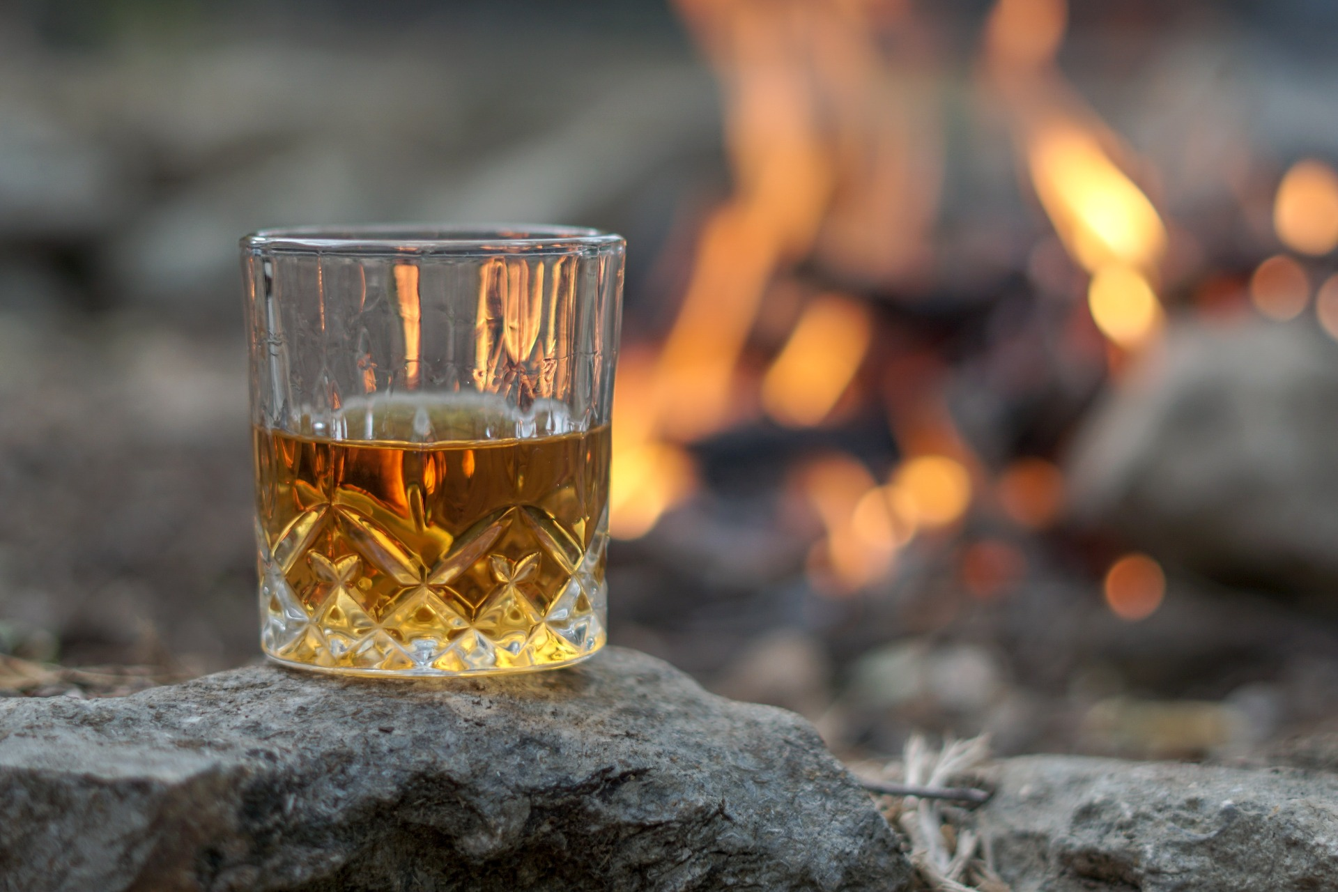 A glass of whisky in front of a fire