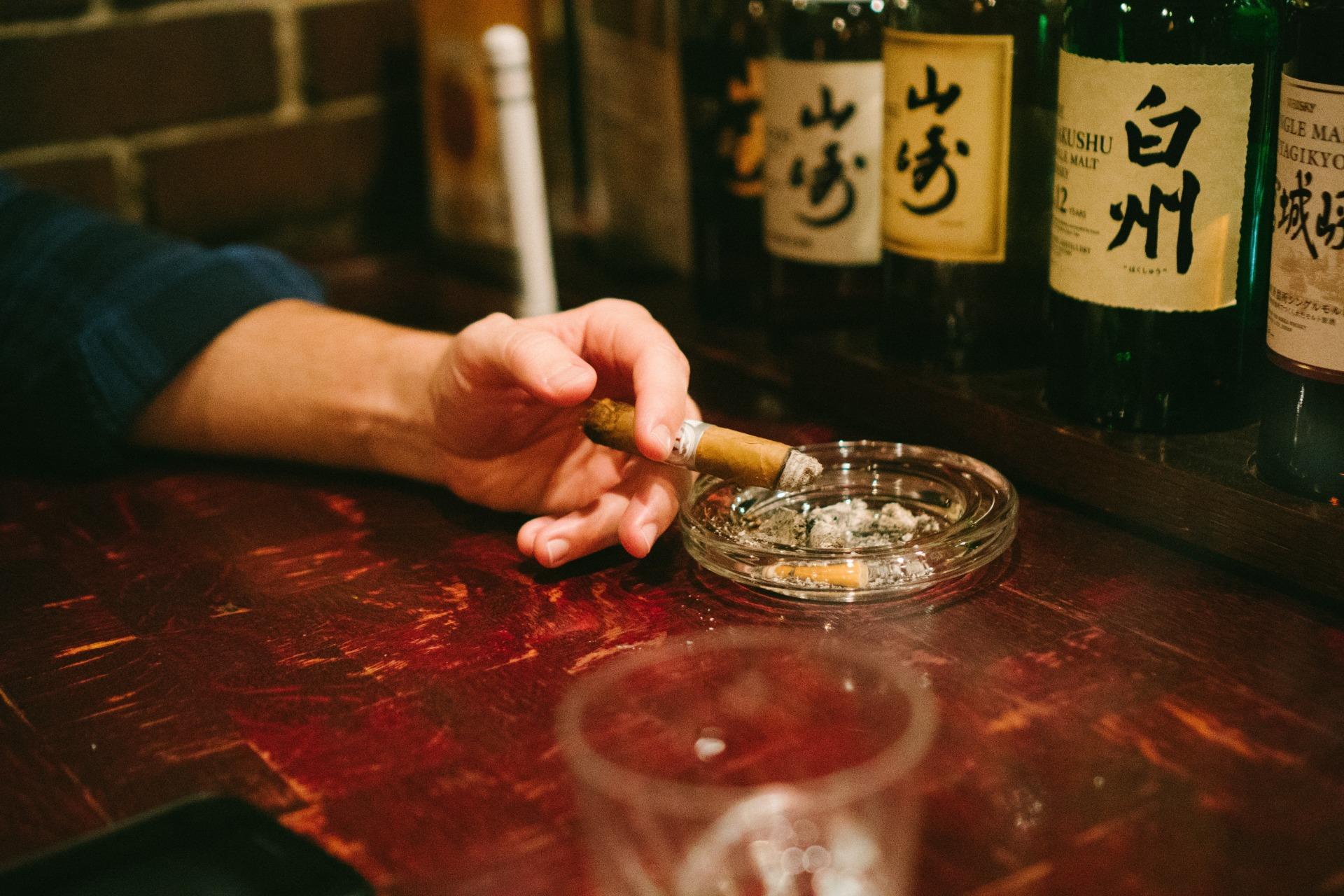 A cigar and an ashtray on a bar