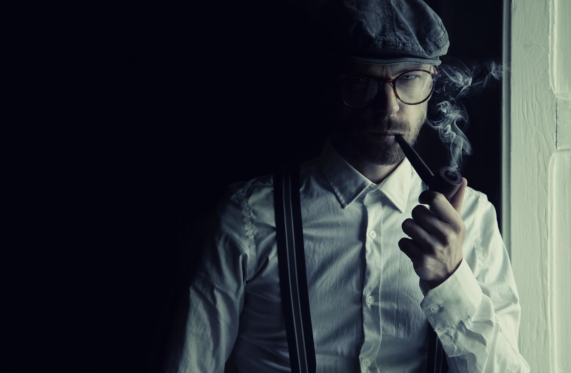 a man in a flat cap smoking a pipe