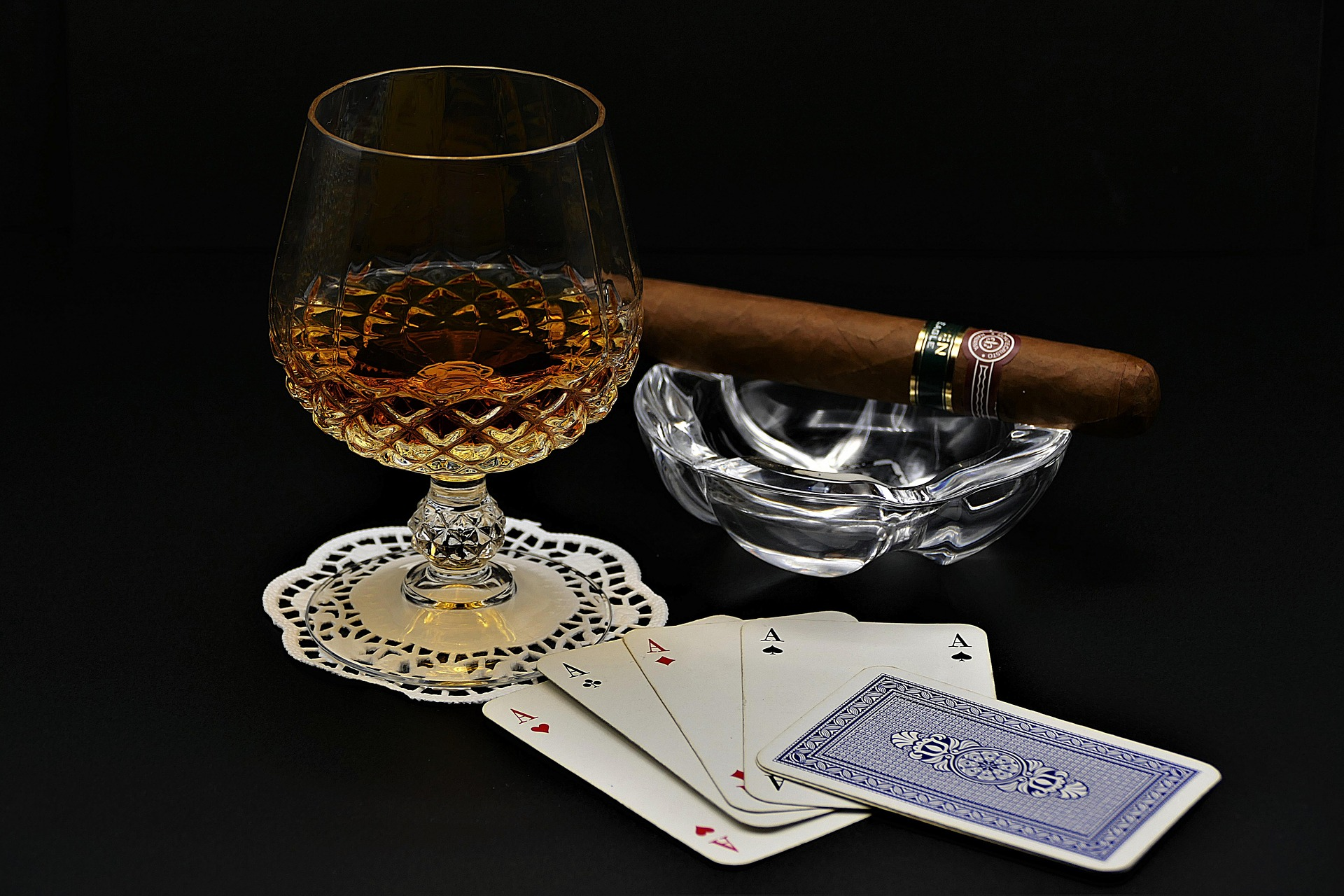 Whisky, poker cards and cigars on a table
