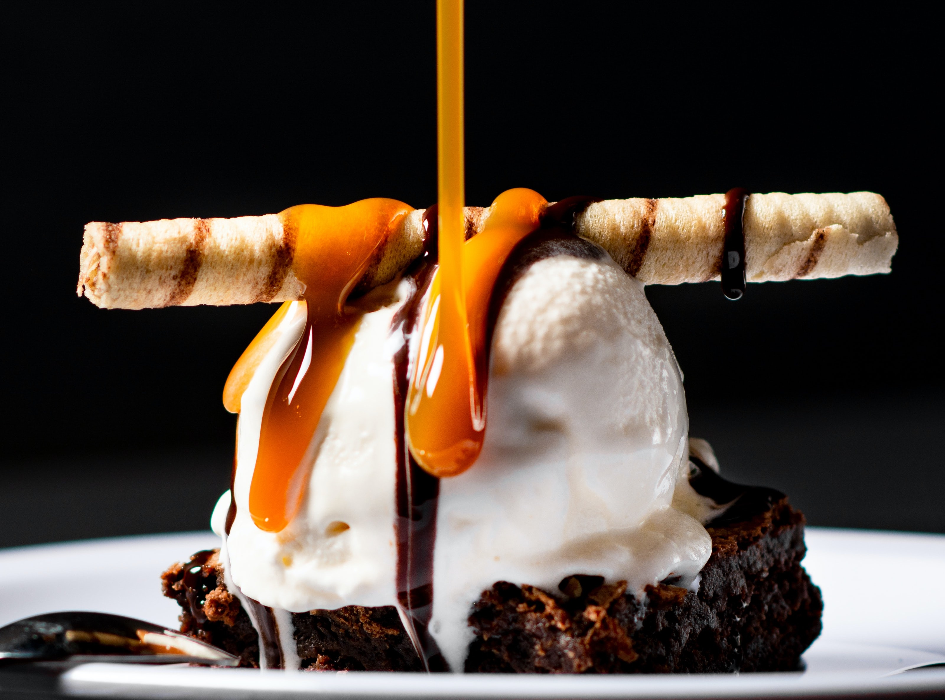 A chocolate brownie with ice cream and a wafer cigar