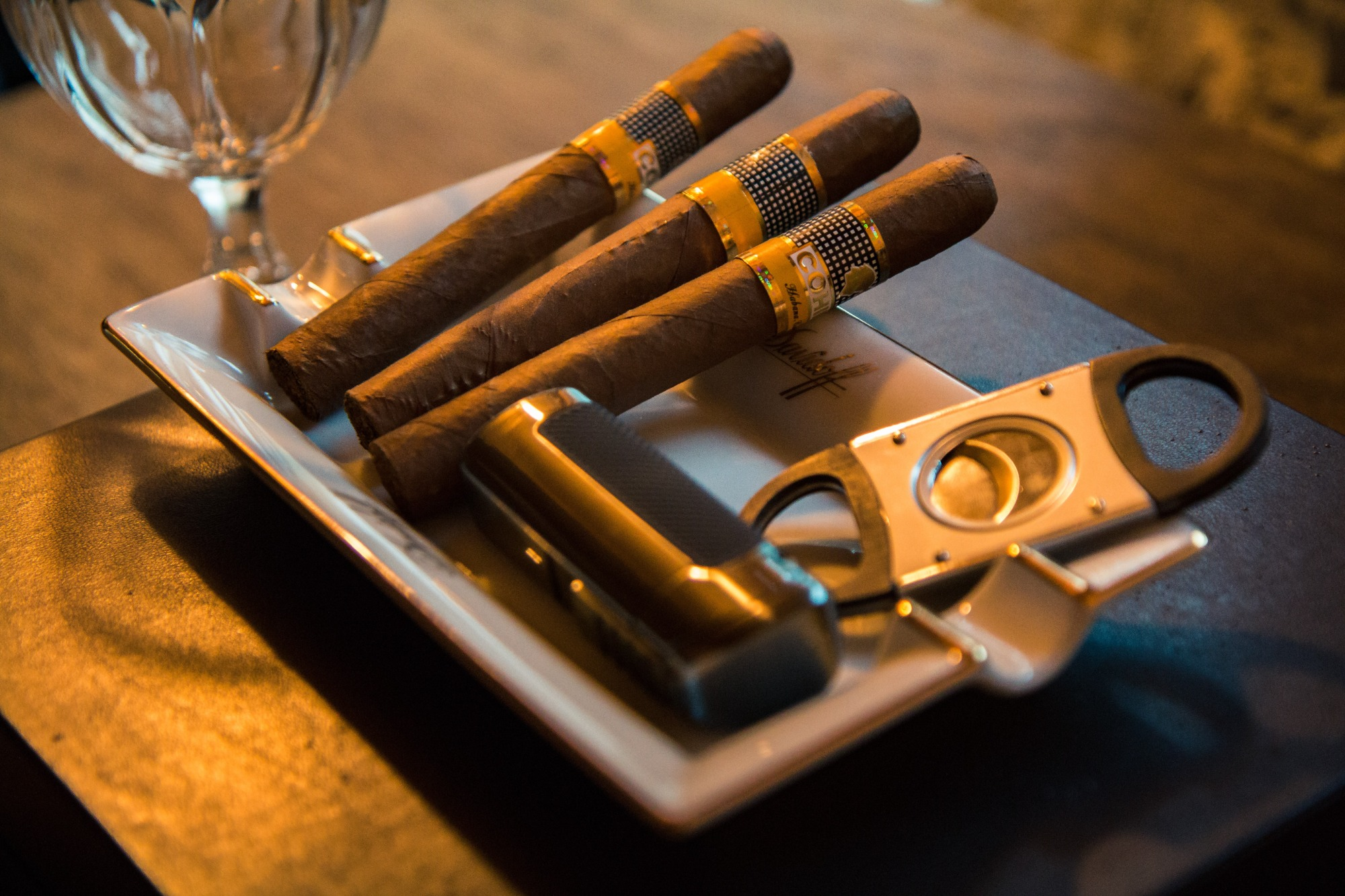 Three cigars, a cigar cutter and a lighter in an ashtray