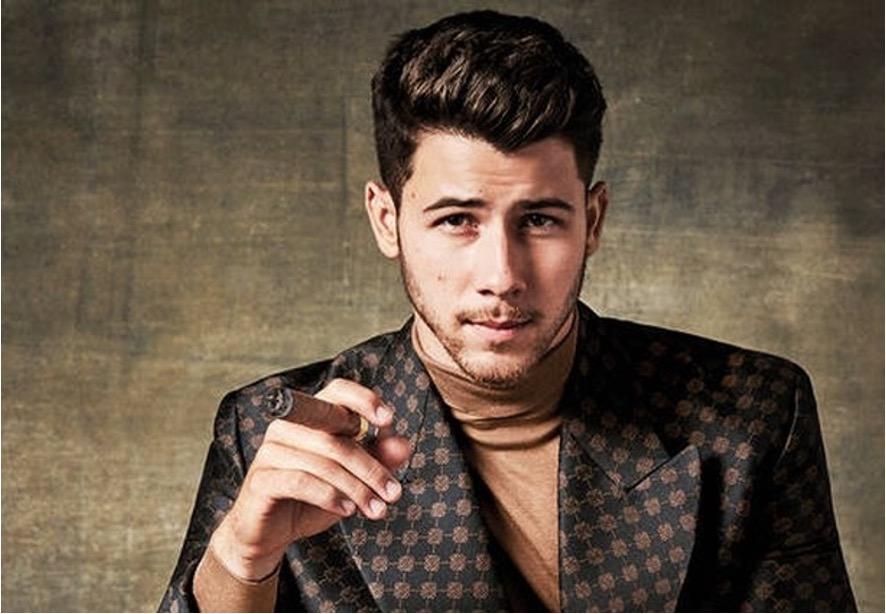 Nick Jonas holding a cigar