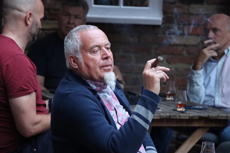 A man at a cigar event holding a lit cigar