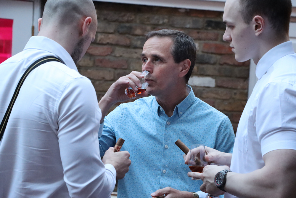 Three men holding cigars and drinking rum
